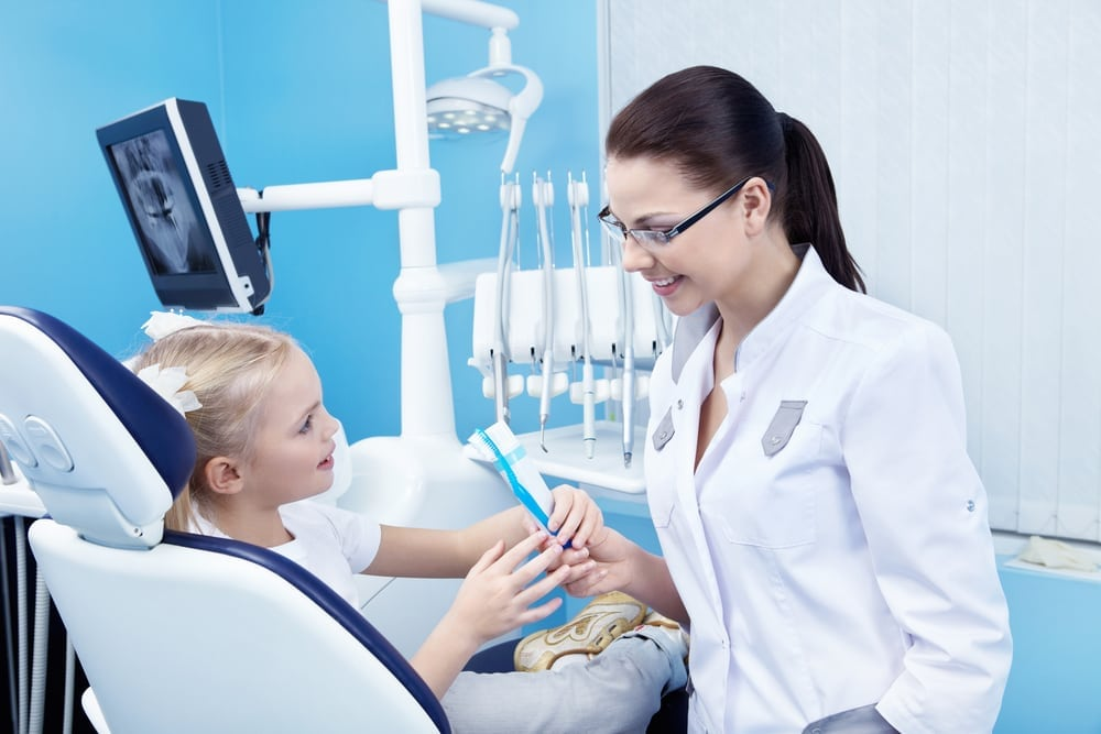 Child sitting in dental chair speaking to her dentist